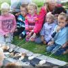 Kinderen zitten rondom de stookplaats om broodjes te bakken